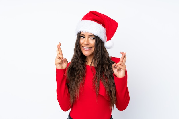 Девушка с шляпой рождества над изолированной белизной с скрещиванием пальцев