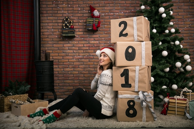 Девушка с рождественскими подарками от елки