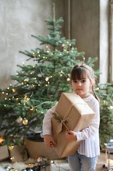 クリスマスツリーとプレゼントを持つ少女