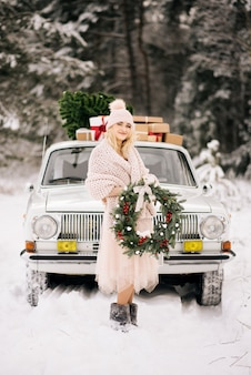 A girl with a christmas wreath in her hands covered with a retro car on a snow forest