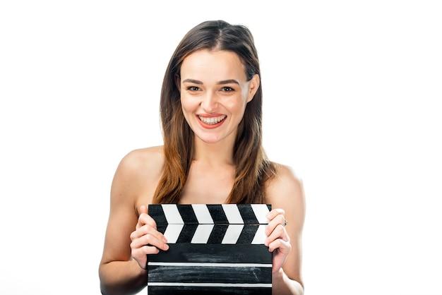 클 래퍼 보드와 소녀입니다. 사람들의 감정. 격리 된 배경입니다. 확대. 필름 분자가 있는 아름다움. 좋은 미소를 가진 갈색 머리입니다. 확대.