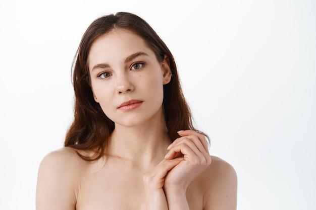 きれいな潤いのある肌、自然な顔のメイク、正面を見て、白い壁に裸の肩を立てている女の子