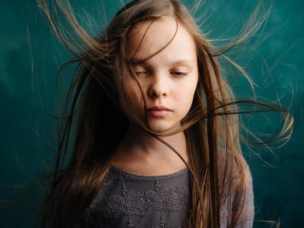 닫힌 눈과 느슨한 머리를 가진 소녀는 고립 된 배경을 닫습니다