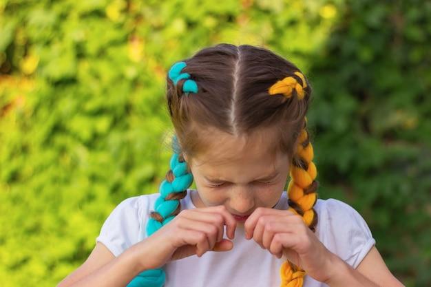 目を閉じた女の子が鼻をこすります。季節性アレルギーの概念。動揺した女の子。くしゃみと咳。