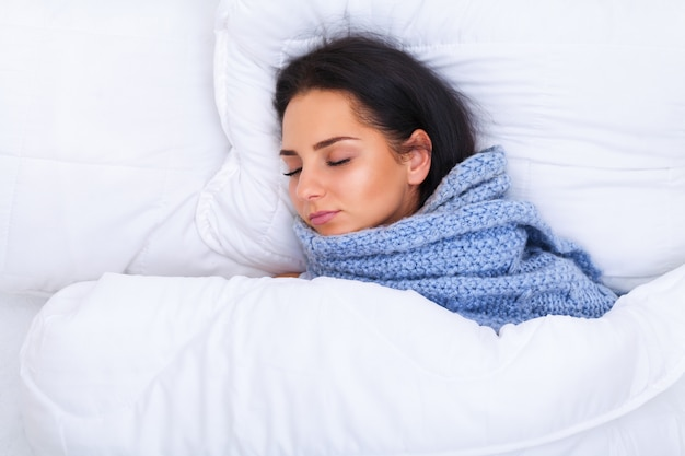 Girl with cold lying under a blanket