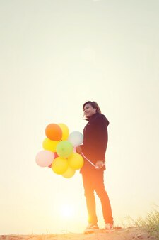 Girl with coloful balloons in sunset