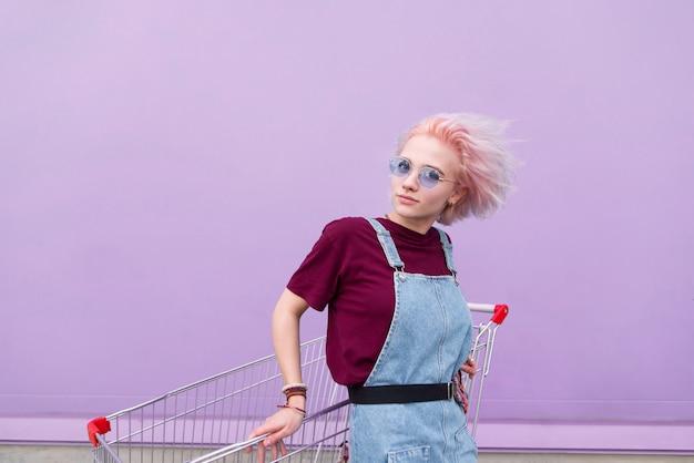 Девушка с цветными волосами и очками позирует в камеру на фоне фиолетовой стены