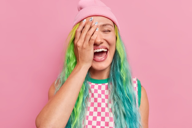 Girl with colored hair piercing in nose cons face with hand expresses positive emotions laughs happily wears hat checkered dress isolated on pink