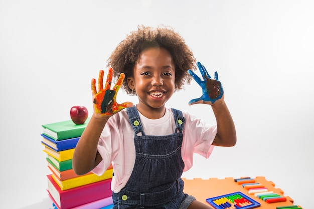 Girl with colored hands with paint in studio