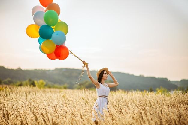 ライ麦畑でカラフルな気球を持つ少女。夏の草原のきれいな女性