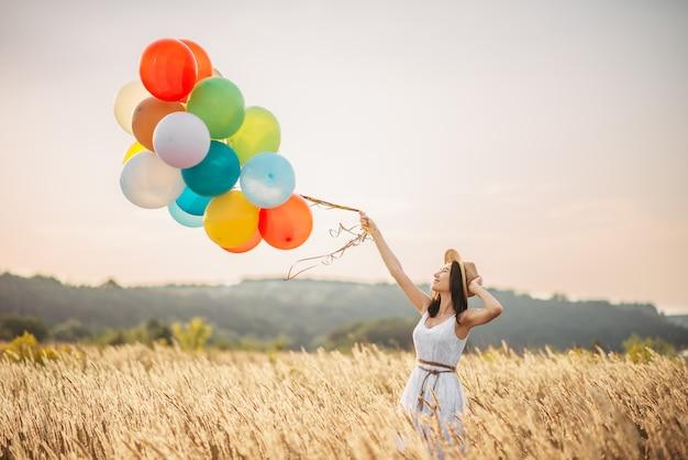 ライ麦畑でカラフルな気球を持つ少女