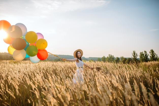 麦畑を歩いてカラフルな気球を持つ少女。晴れた日に夏の草原のきれいな女性