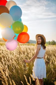 麦畑を歩いてカラフルな風船を持つ少女、背面図。晴れた日に夏の草原のきれいな女性