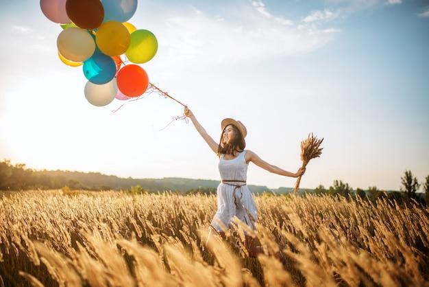 麦畑を歩いてカラフルな風船を持つ少女