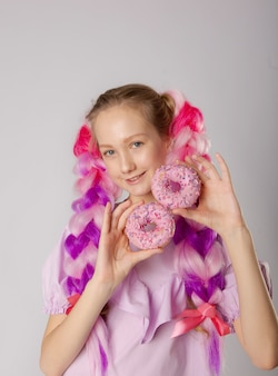 Girl with colorful braids and doughnuts