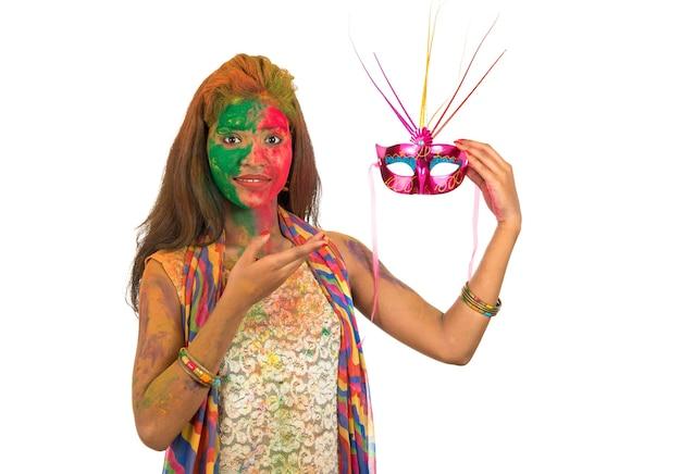カーニバルマスクを保持し、ホーリーを祝うカラフルな顔を持つ少女。