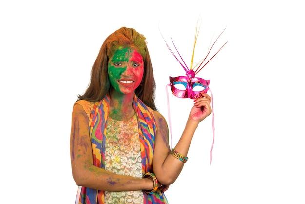 Девушка с красочным лицом держит карнавальную маску и празднует холи.
