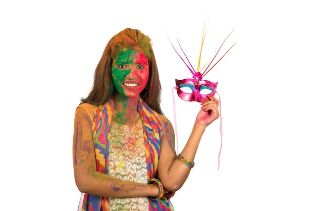 Girl with colorful face holding carnival mask and celebrating holi.