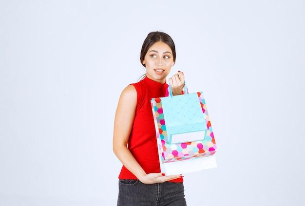 Ragazza con borse della spesa colorate sensazione positiva.