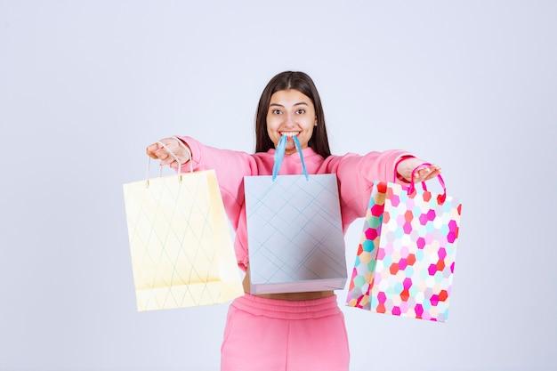 Ragazza con borse della spesa colorate tenendole nelle mani e in bocca.