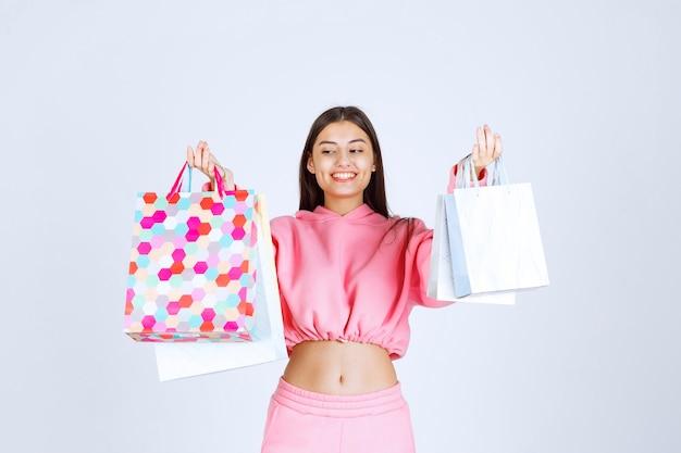 다채로운 쇼핑 가방을 가진 소녀는 행복하고 만족해 보입니다.
