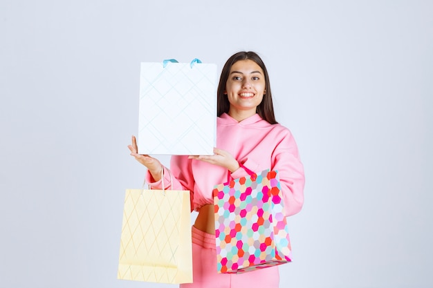 Girl with colorful shopping bags looks happy and satisfied.