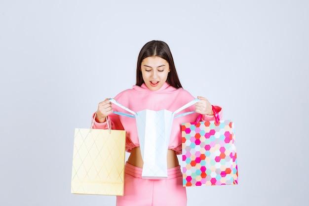Ragazza con borse della spesa colorate aprendole e controllando.