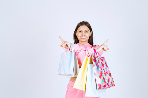 Girl with colorful shopping bags pointing left and right sides.