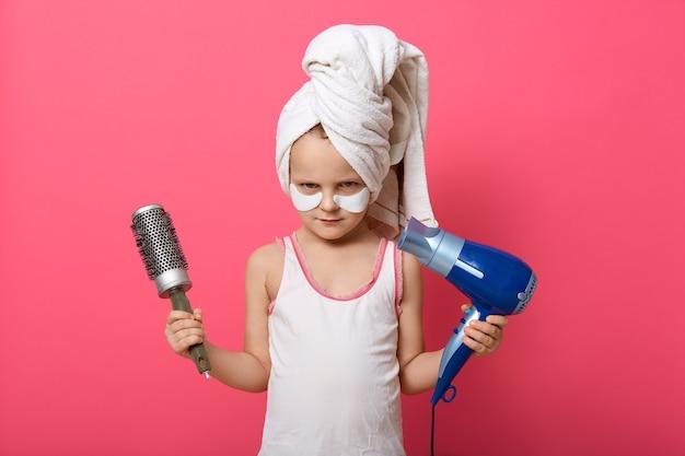 恥ずかしがり屋の表情でカメラを直接見ている櫛と髪の毛が乾いた女の子