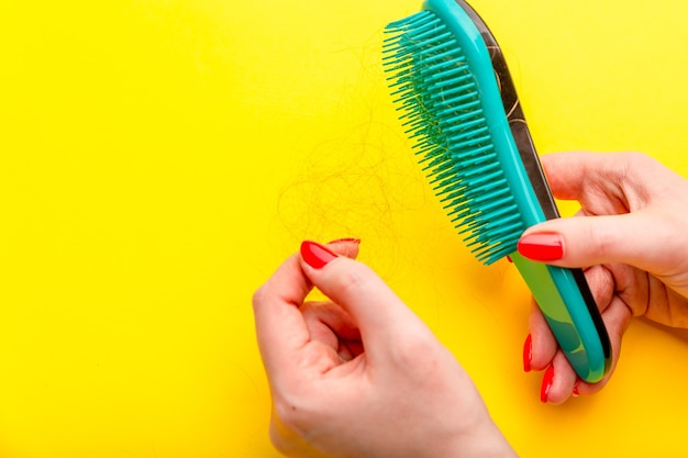 Girl with a comb and problem hair on white background.