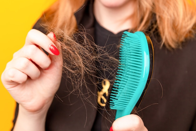 Girl with a comb and problem hair on the yellow wall.