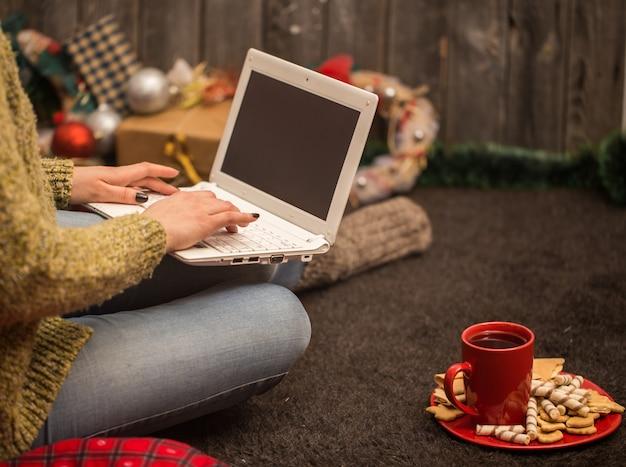 コンピューターのクリスマスの装飾を持つ少女
