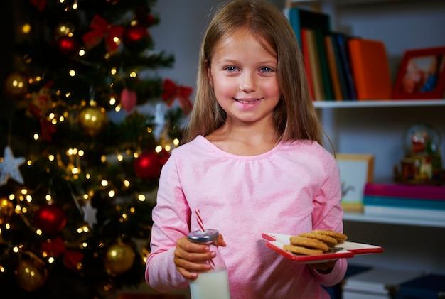 クッキーと牛乳を持つ少女サンタクロースを待っています