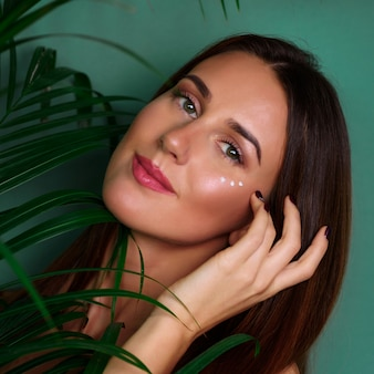 Girl with cream dots on her face between palm leaves on green background