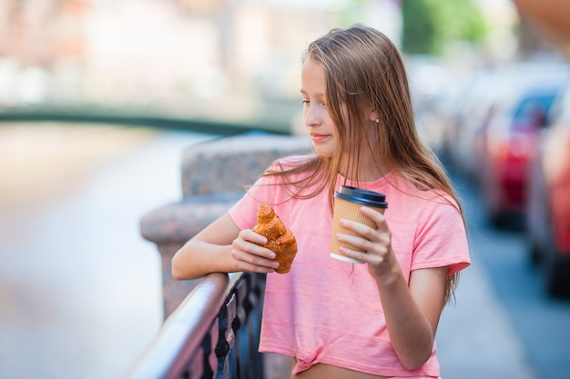 Girl with a croissant and coffee outdoors on the promenade