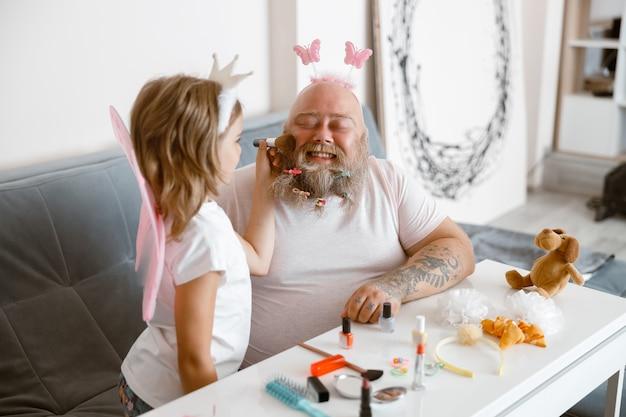 Девушка с короной и крыльями наносит пудру на лицо отца в современной гостиной