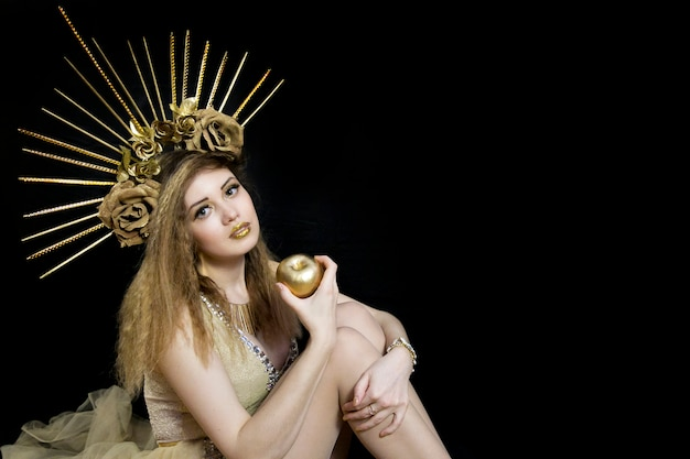 Girl with a crown on his head and golden apple