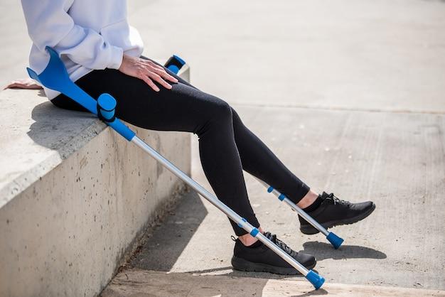 ベンチで彼女の足を休んで松葉杖を持つ少女