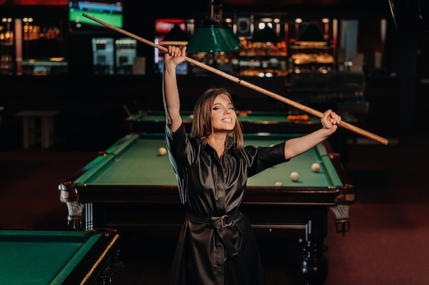 A girl with a cue in her hands is standing in a billiard club