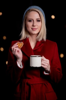 Girl with cup of coffee and gingerbread cookie