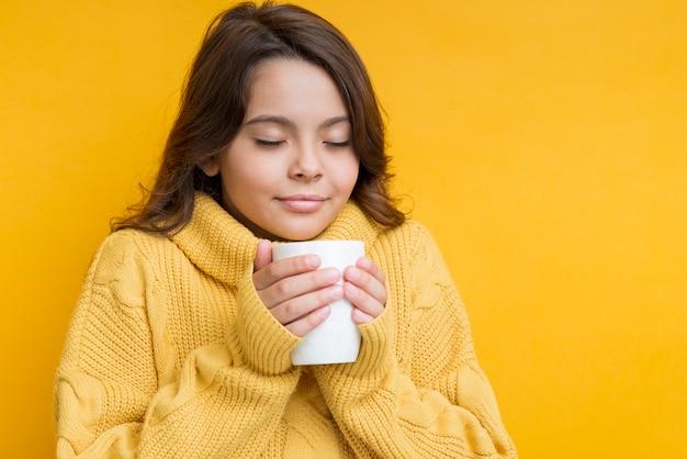 Девушка с чашкой в руках и закрытыми глазами