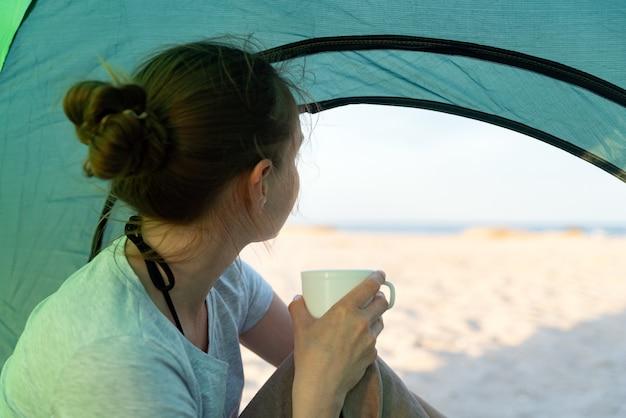 手にカップを持つ女の子はテントに座って、ビーチと海を見ます