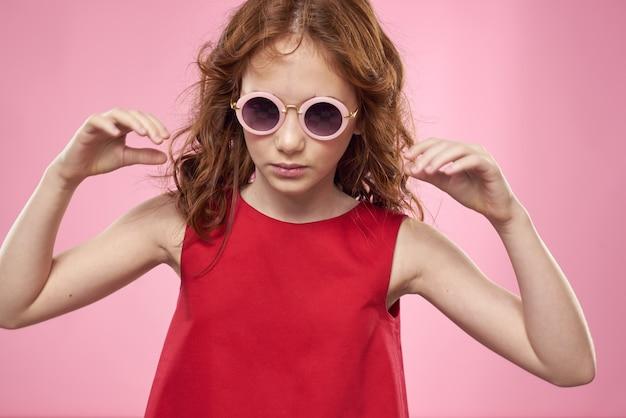 곱슬 머리를 가진 소녀 어두운 둥근 안경 재미 빨간 드레스 핑크