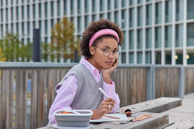 巻き毛の女の子は彼女の将来のプロジェクトのためにスケッチを描きますペンは色鉛筆を使用し、大きな丸い眼鏡のシャツを着て、モダンな建物に対して屋外でニットのベストのポーズをとります