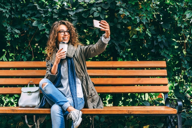 Girl with curly hair drink coffee and use smartphone outdoor