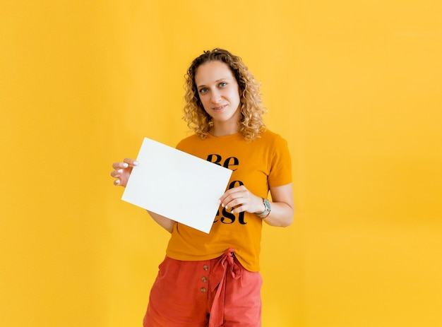 Girl with curly hair holding a blank card. isolated on yellow background smiling woman portrait.