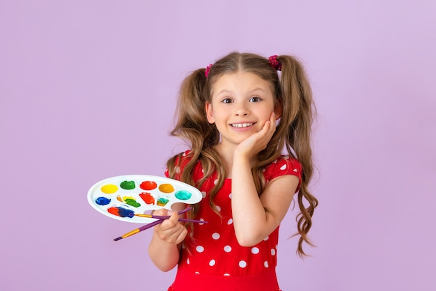 A girl with curly hair holds a paint palette and a brush in her hands.