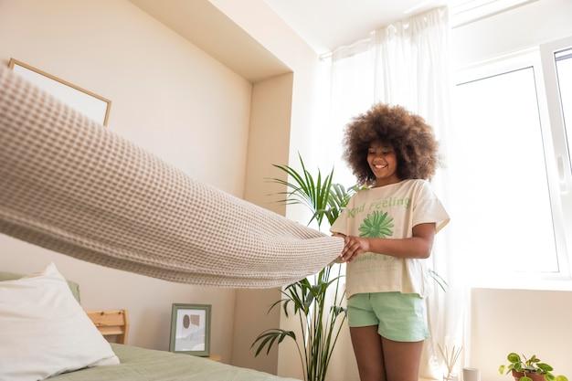침대를 만드는 곱슬 머리를 가진 소녀