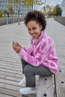 곱슬머리 소녀 미소 기쁜 마음으로 휴대전화 들고 행복을 표현합니다 낮에 야외에서 포즈 좋은 날씨 검색 정보 읽기 문자 메시지