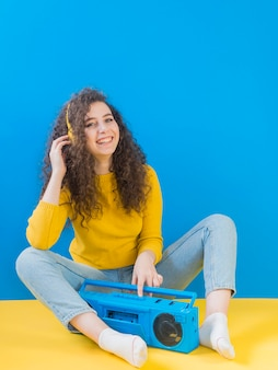 Girl with curly hair smiles and listening to music